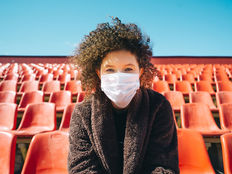 Woman%20in%20a%20surgical%20mask%20sitting%20in%20an%20empty%20stadium